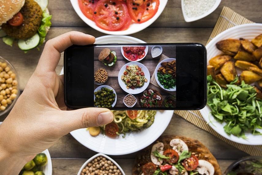 יד עושה תצלום של שולחן מלא באוכל מסוגים שונים
