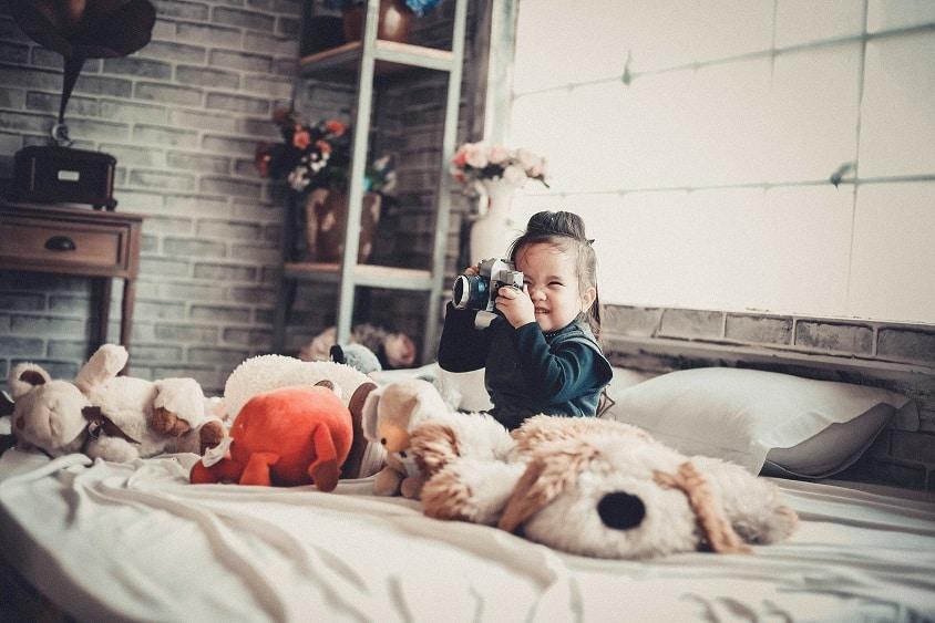 ילדה אסייתית קטנה יושבת על מיטה עם הרבה בובות צעצוע ומחזיקה מצלמה