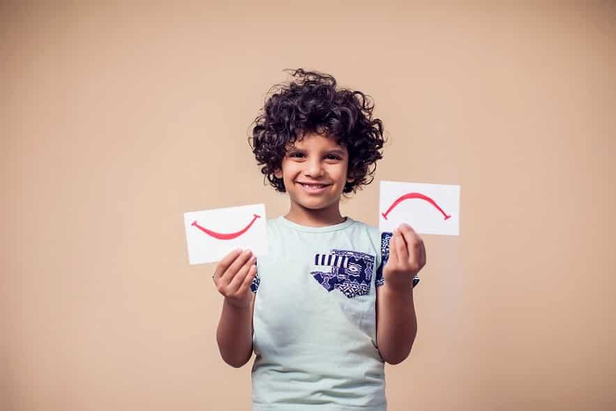 ילד מתולתל מחזיק דפים שמצויירים עליהם צורות שונות