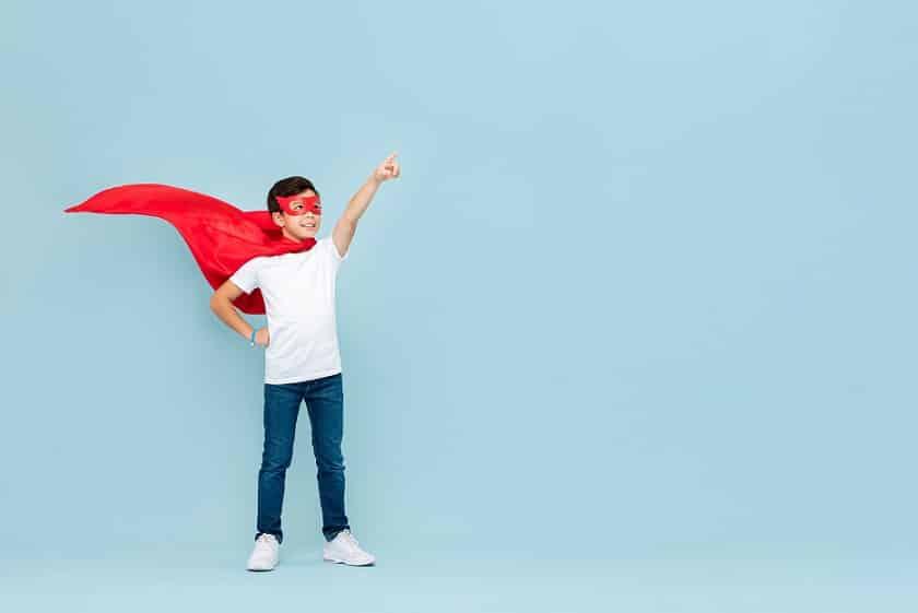ילד קטן עם גלימה של גיבור על עושה תנועה עם היד