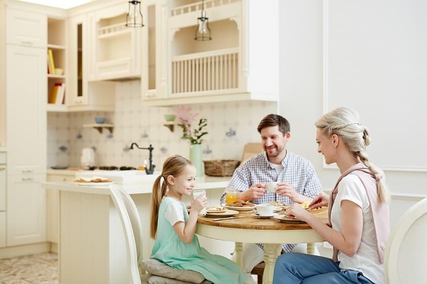 משפחה צעירה עם ילדה יושבת לאכול ארוחת צהריים במטבח
