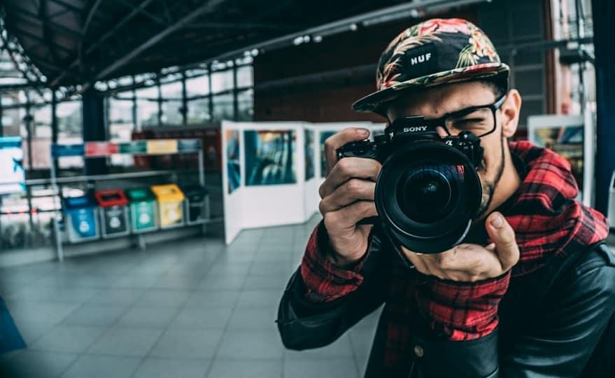 צלם עם קובע אופנתי מצלם את המסך ועוצם עין אחת בשדה תעופה