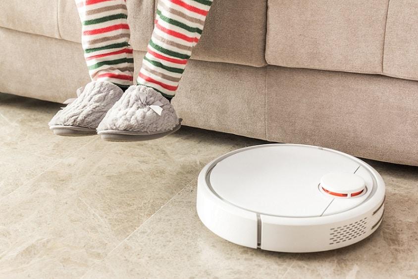 שואב רובוטי לבן מנקה את הרצפה עם רגליים ברקע