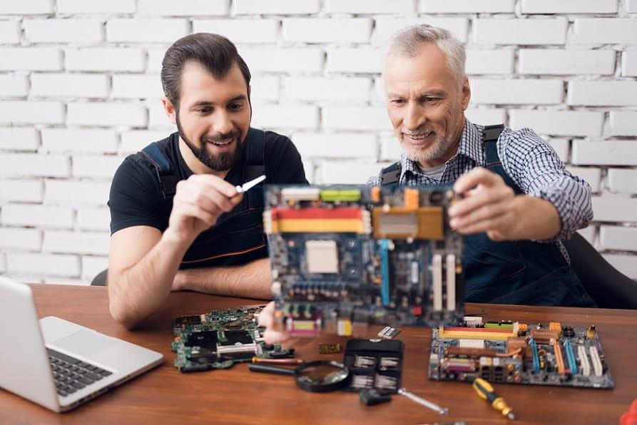 2 טכנאים בודקים חומרה של מחשב מפורק