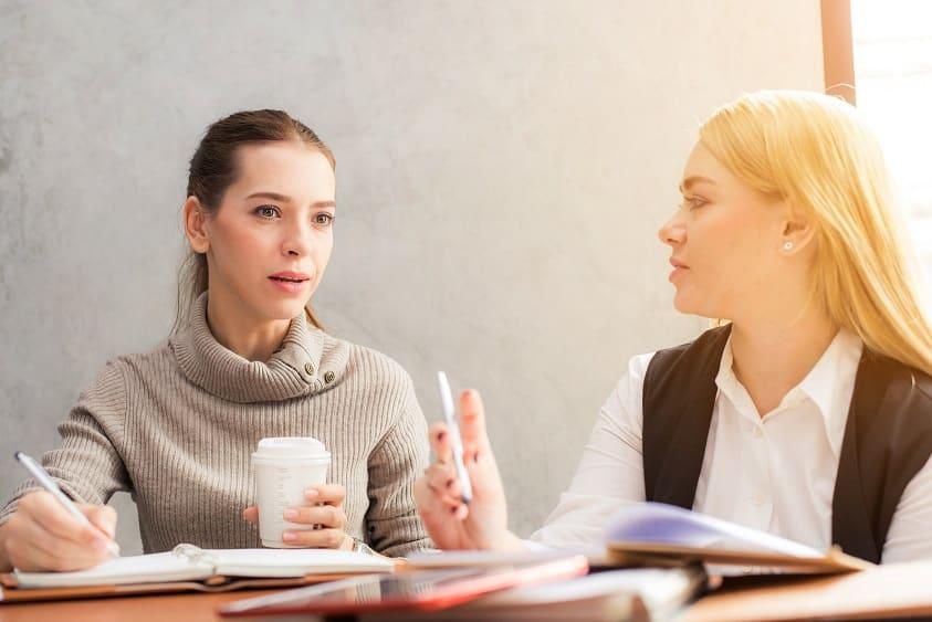 2 נשים יושבות בשולחן ודנות על נושא מסויים תוך כדי רשימה של דברים במחברת
