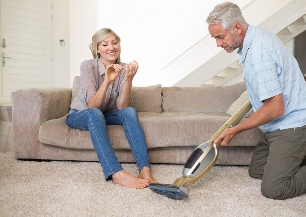 אישה יושבת על הספה בזמן שהגבר מנקה את השטיח