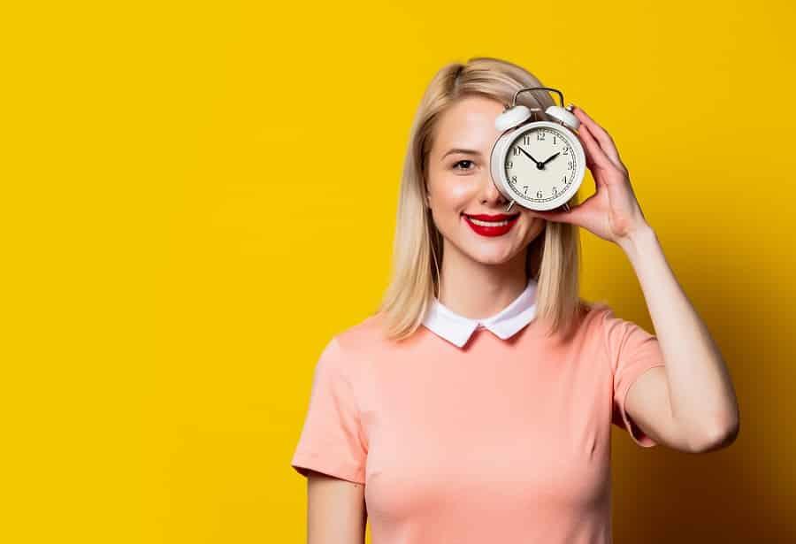 אישה צעירה עומדת על רקע צהוב ומסתירה את אחת העיניים שלה