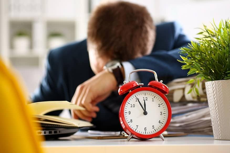 איש עסקים צעיר נרדם על שולחן העבודה שלו בין המסמכים