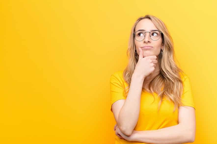 בחורה בלונדינית עם שיער ארוך ומשקפיים עושה מבט של שאלה