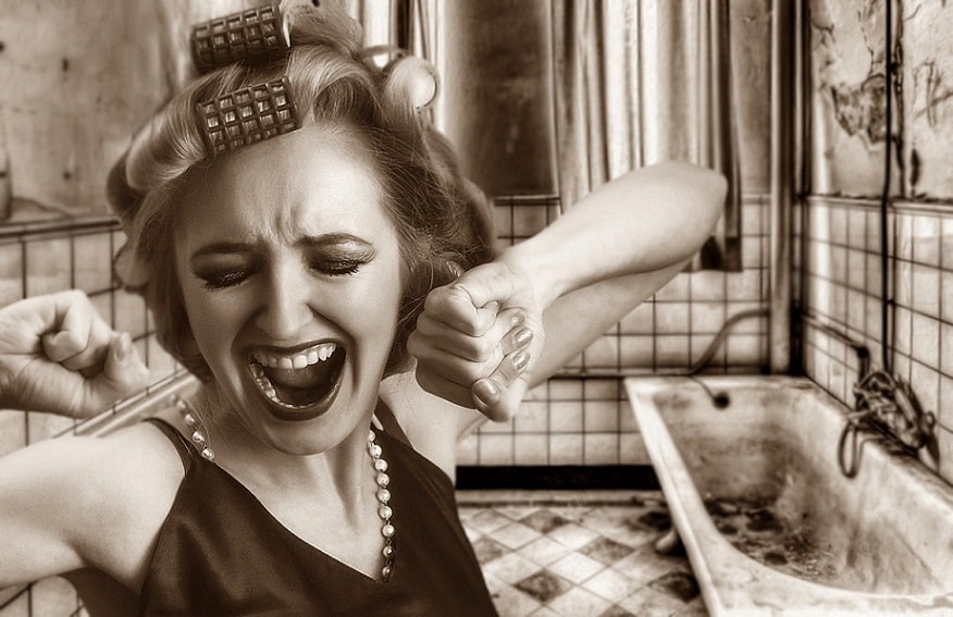 בחורה מסרט עם רולים בשיער צועקת באמבטיה ישנה והרוסה