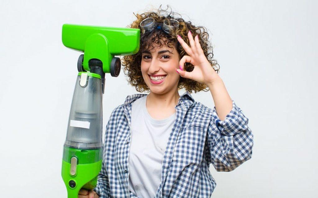 בחורה עם תלתלים מחייכת למצלמה ועושה סימן של פיקס עם היד