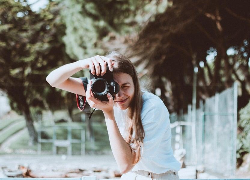 בחורה צלמת צעירה מצלמת את המסך עוצמת עין אחת