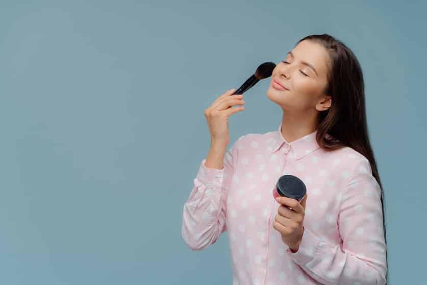 בחורה צעירה מברישה את הפנים שלה עם מברשת איפור