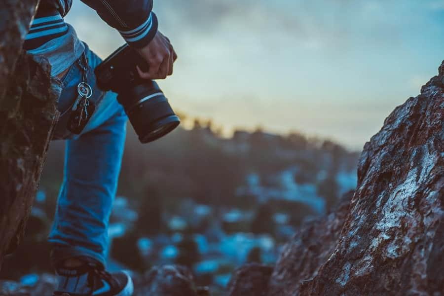 בחור יושב בטבע בין הרים עם מצלמה ביד ומסתכל לאופק
