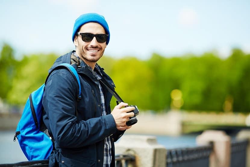 בחור עם כובע כחול מטייל עם המצלמה שלו ומחייך למסך