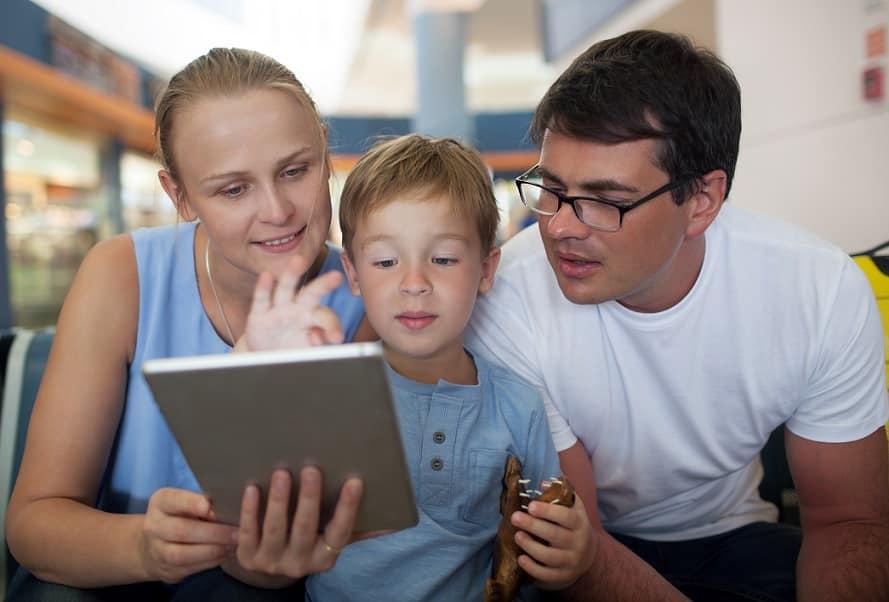 זוג הורים והבן הקטן שלהם מסתכלים על מסך של טאבלט