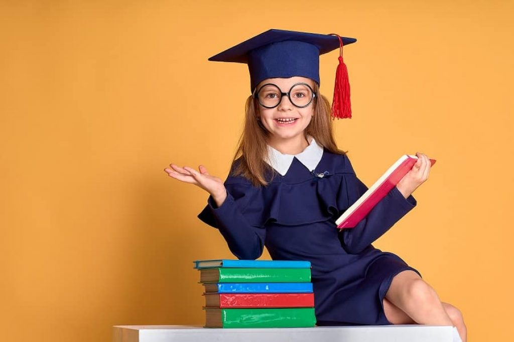 ילדה קטנה בבגדים של סטודנטים עונה על שאלות