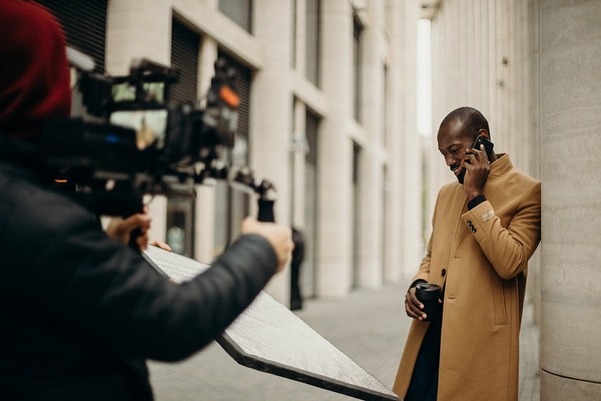 צלם מצלם גבר שמחזיק כוס משקה מדבר בפלאפון ונשער על בניין ברחוב