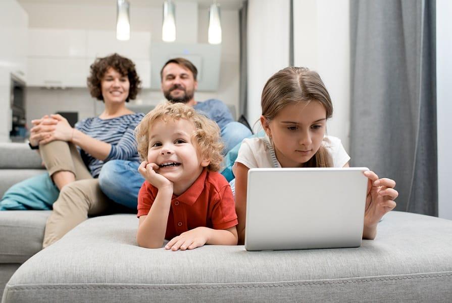 אח ואחות קטנים מסתכלים במחשב בזמן שההורים יושבים מאחורה