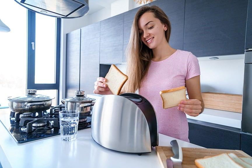 בחורה מכניסה צנימים לתוך מנצם במטבח