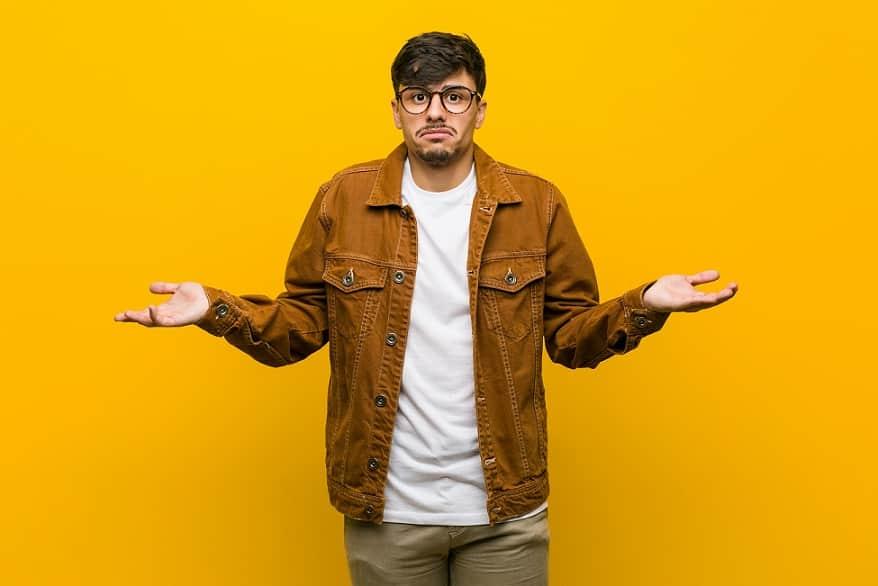 בחור היספני עם משקפיים עושה תנועה של שאלה