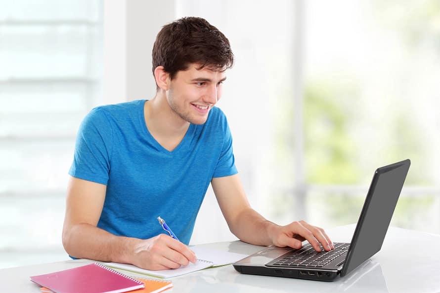 בחור צעיר בחולצה כחולה יושב מול מחשב מחייך ורושם הערות