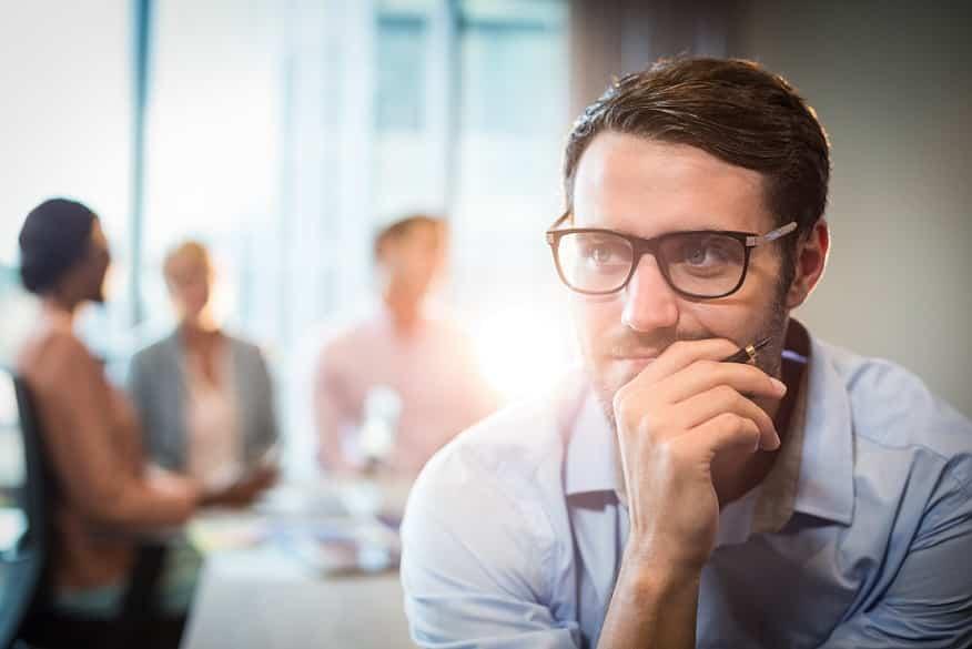 גבר עם משקפיים מחזיק את הסנטר וחושב על משהו