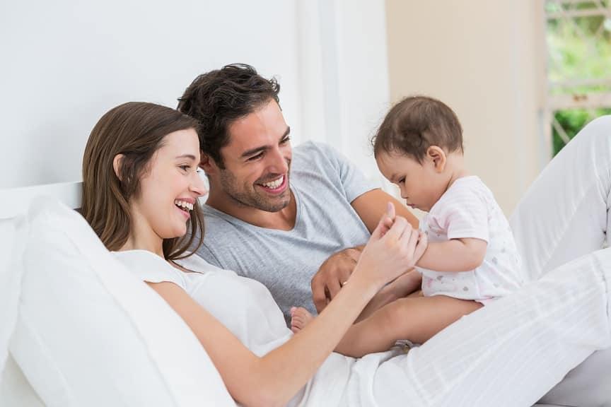 זוג הורים צעירים משחק עם התינוק שלהם במיטה
