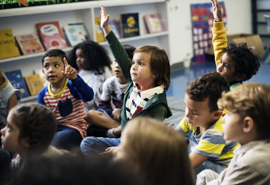 ילדים בגן מצביעים כדי לשאול שאלה את הגננת
