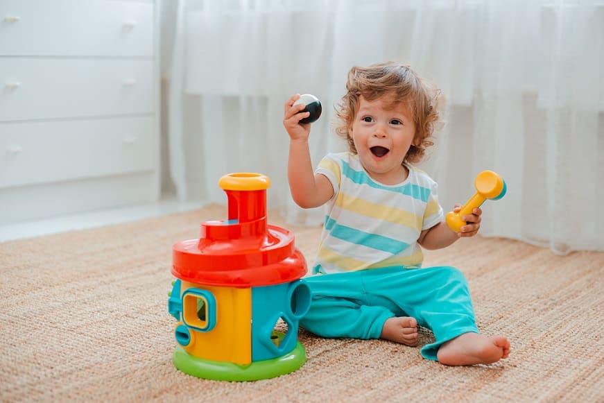 ילד קטן עם מבט מופתע משחק עם צעצועים שונים על הרצפה