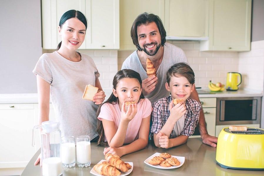 משפחה עומדת במטבח ואוכלת מאפים שונים מכל הסוגים