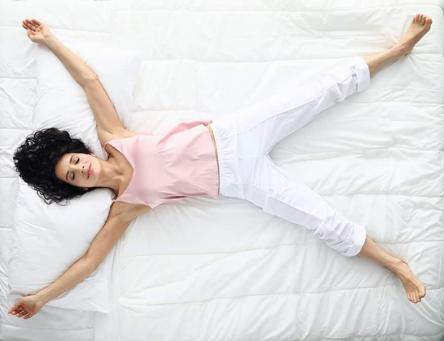 אישה עם עיניים עצומות שוכבת על המיטה וחולמת