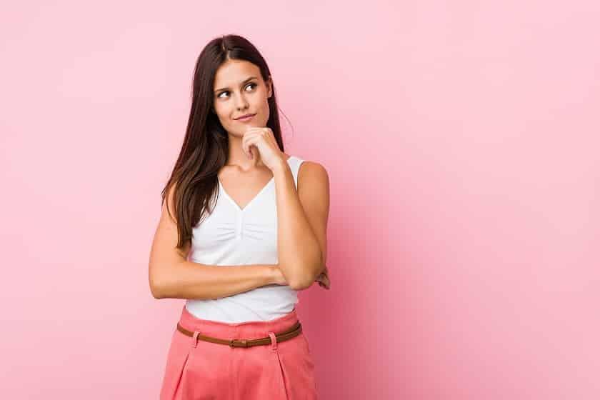 בחורה צעירה עם חולצה קצרה חושבת על שאלה על רקע ורוד