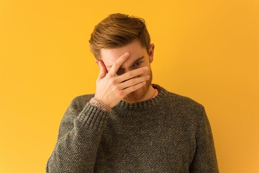 בחור בלונדיני צעיר מכסה את הפנים שלו עם היד בגלל בושה