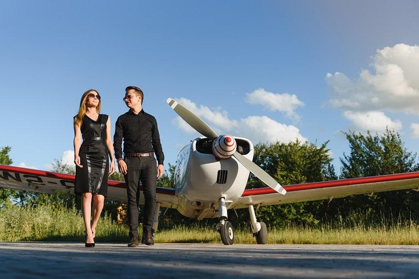 גבר ואישה מצליחים עומדים על רקע של מטוס פרטי