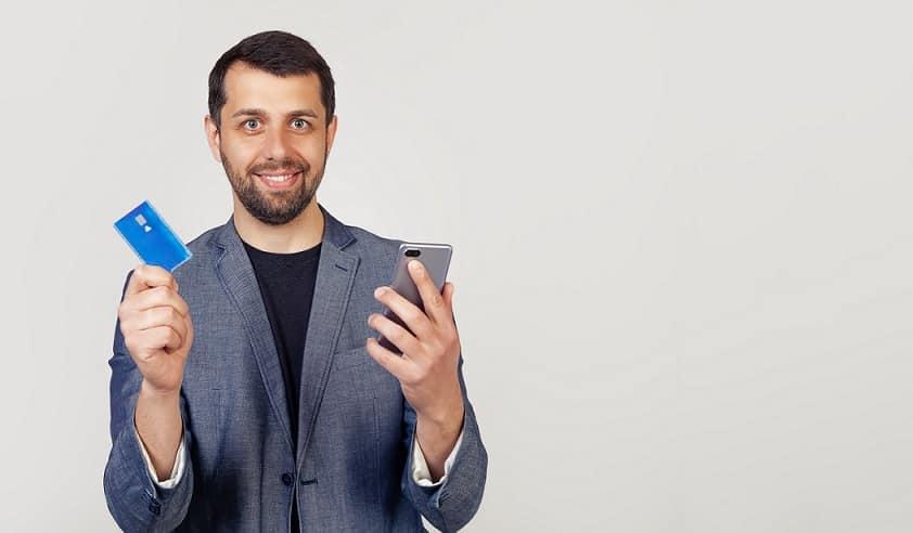 גבר מחזיר כרטיס אשראי ביד אחת וסמארטפון ביד השניה