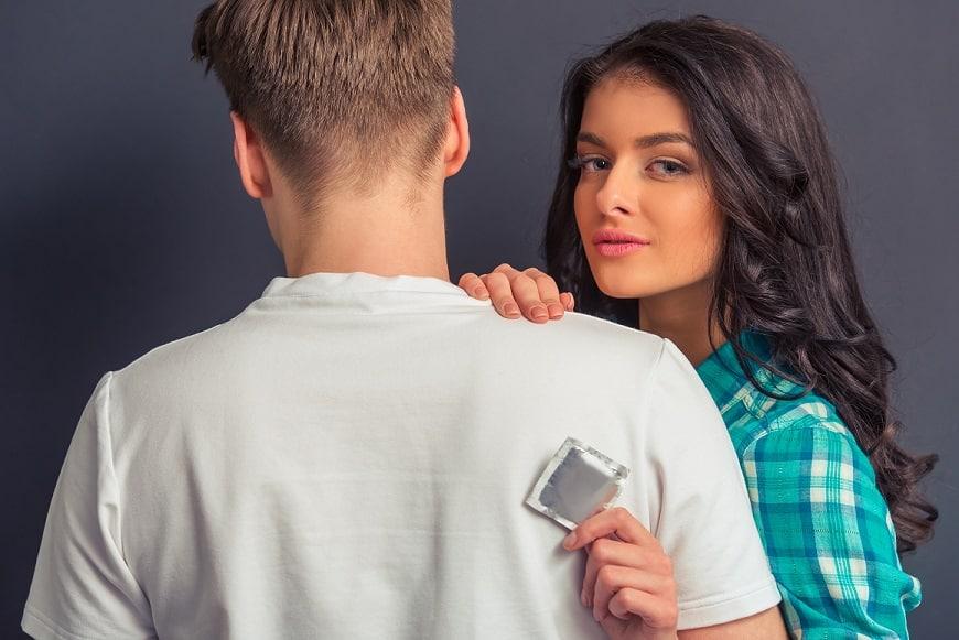 זוג מתחבק בזמן שהבחורה מחזיקה אריזה של קונדום