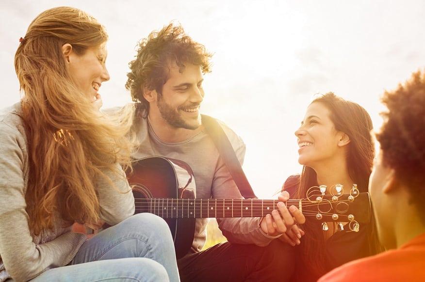 חבורה של חברים יושבים ביחד בחוץ ושרים שירים עם גיטרה