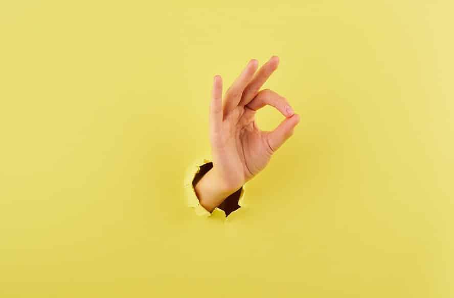 יד פורצת מתוך רקע צהוב ועושה סימן של הכל מעולה