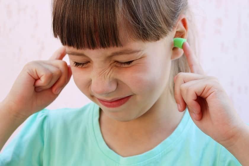 ילדה קטנה עם אטמי אוזניים בצבע ירוק עושה פרצוף זועף