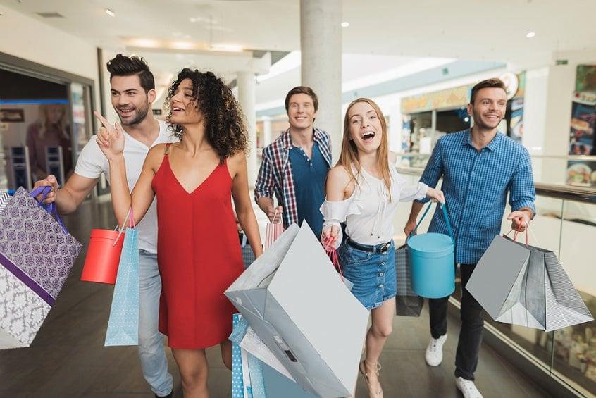 קבוצה של 5 חברים עושים קניות בקניון עם שקיות מלאות במוצרים