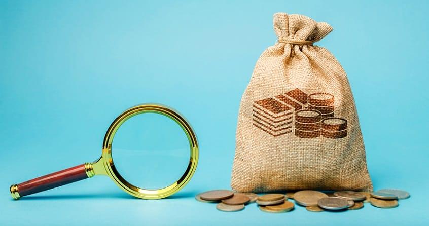 שק של מטבעות ליד זכוכית מגדלת על רקע טורקיז בהיר