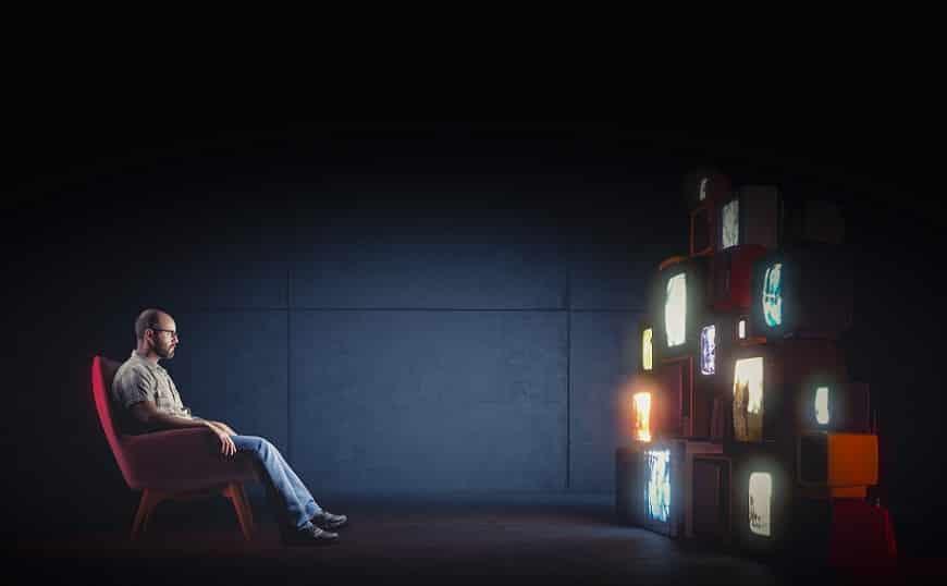 אדם יושב ובוהה בהרבה מסכי טלוויזיה מסוגים שונים