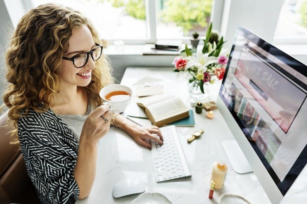 אישה עם תלתלים שותה משקה חם ומסתכלת על המסך של המחשב