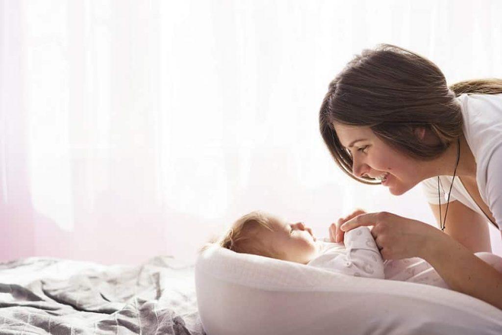 אמא משחקת עם התינוק שלה כשהוא במיטה הקטנה שלו