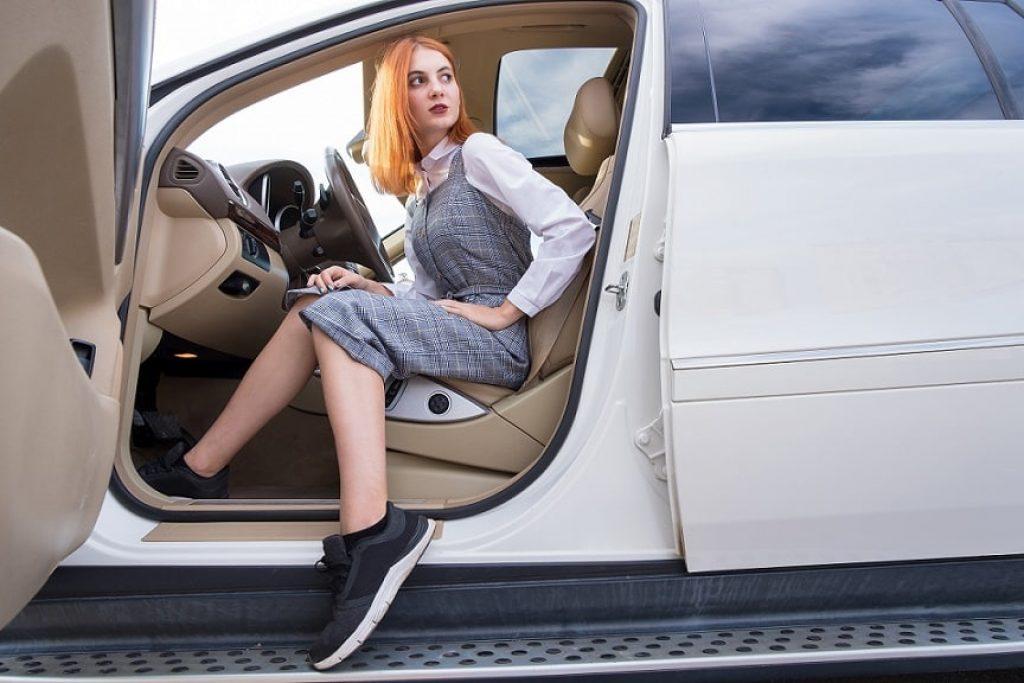 בחורה צעירה ועשירה לובשת בגדי מותגים ויושבת ברכב יוקרתי