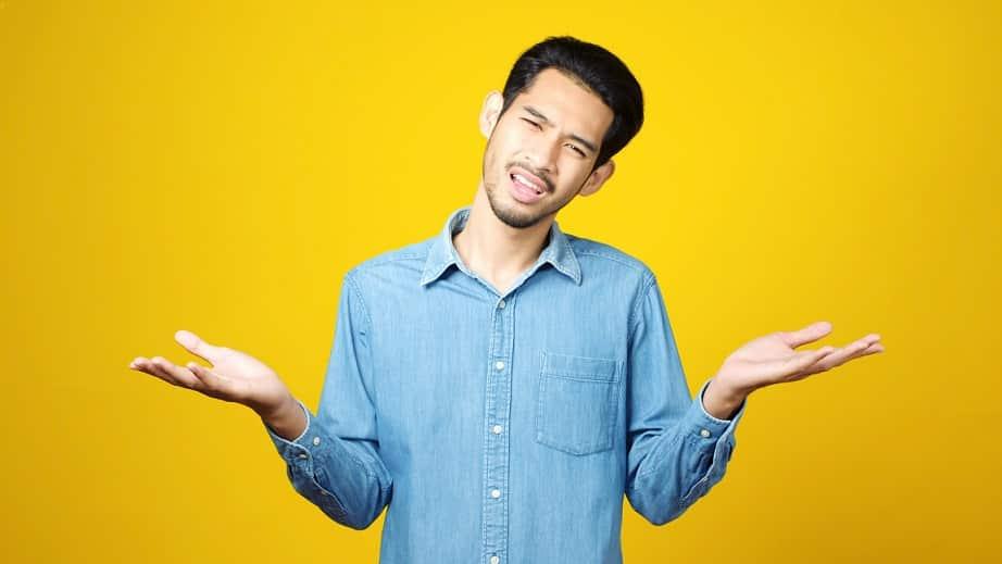 בחור אסייתי צעיר עושה תנועה של שאלת שאלה על רקע צהוב