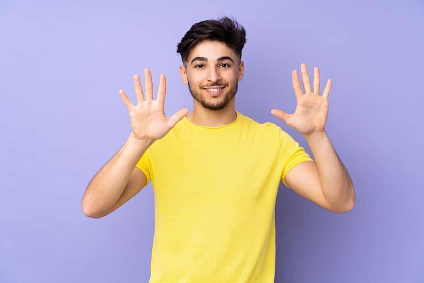 בחור צעיר עם חולצה צהובה עושה סימן של 10 עם הידיים