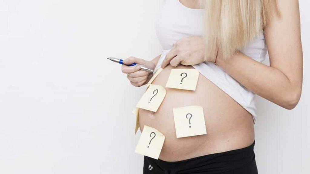 בטן הריונית של אישה עם סימני שאלה מצוירים