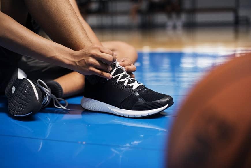 גבר יושב על הרצפה באולם ספורט וקושר נעלי כדורסל